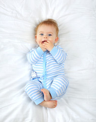 A charming blue-eyed 7 month old baby lies in bed in a striped bodysuit and sucks his fingers. Top view