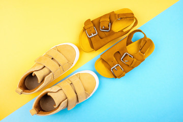 Sneakers and sandals on a trendy background of yellow-blue color, top view, summer shoes. Flat lay. Wall mural