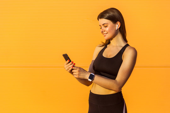 Portrait of young happy attractive sporty woman in black sportwear standing near orange wall background and holding phone, reading message with toothy smile, outdoor on summer, sunshine