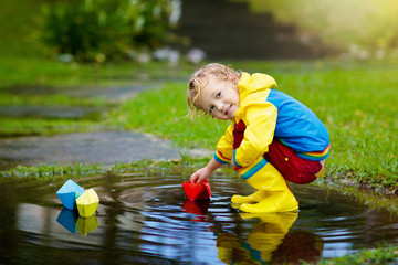 Child playing with paper boat in puddle