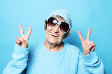 Funny old lady wearing blue sweater, hat and sunglasses showing victory sign. Isolated on blue background. Wall mural
