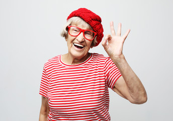 Lifestyle, emotion and people concept: Funny old lady wearing red hat and eyeglasses showing ok sign