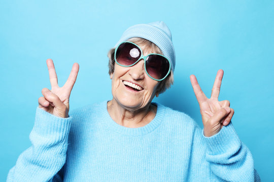 Funny old lady wearing blue sweater, hat and sunglasses showing victory sign. Isolated on blue background.