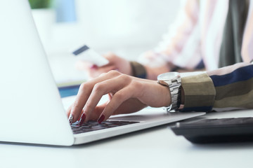 Female office worker hands holding credit card, typing on the keyboard of laptop, online shopping...