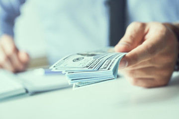 Mid section of a man giving money us dollar banknotes and holding cash in hands. Money credit concept. Toned picture.