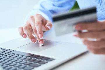 Female hand holding credit card and typing numbers on laptop keyboard while sitting at office table. Selective focus.
