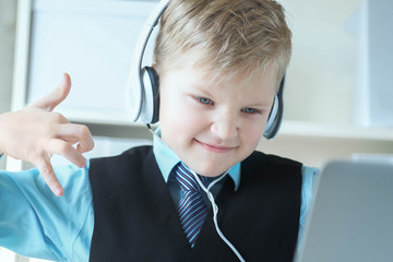 Cute 6 year old boy in suit listening to music or audio tutorial on headphones at the office background.