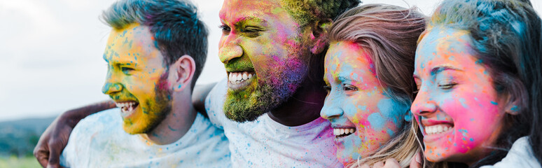 panoramic shot of woman smiling near multicultural friends with holi paints on faces