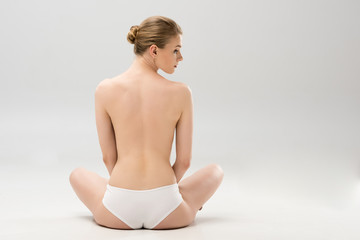 back view of young woman in panties sitting on grey