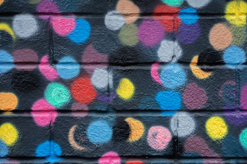 Bricks wall is decorated with bright abstract colored circles on black background closeup. Detail...