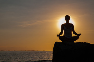 Woman is practicing yoga sitting on stone in Lotus pose at sunset. Silhouette of woman meditating on the beach Wall mural