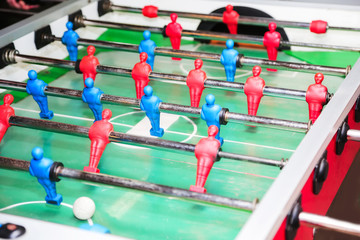 Detail of kid's hands playing the foosball table match. Soccer game, friends recreation