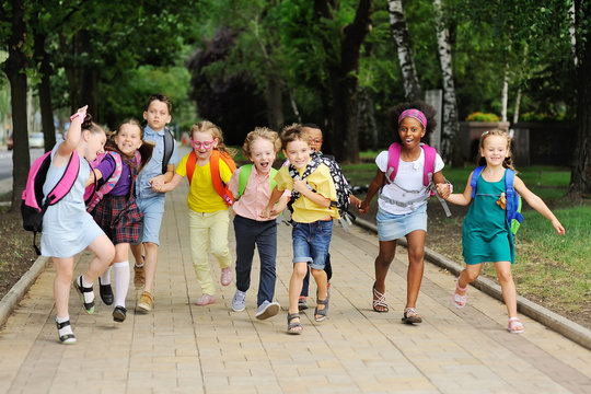 small schoolchildren with colorful school bags and backpacks run to school. Back to school, education, elementary school.