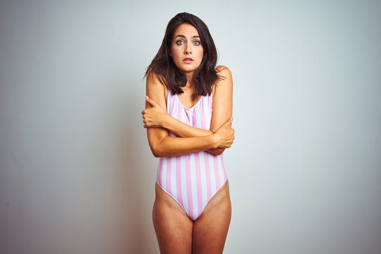 Young beautiful woman wearing striped pink swimsuit swimwear over isolated background shaking and freezing for winter cold with sad and shock expression on face