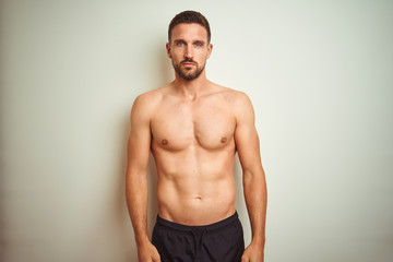 Young handsome shirtless man over isolated background Relaxed with serious expression on face. Simple and natural looking at the camera.