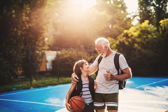 Grandfather and his grandson enjoying together on basketball court.