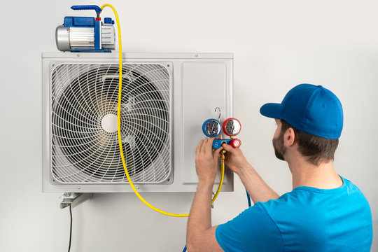 Installation service fix  repair maintenance of an air conditioner outdoor unit, by cryogenist technican worker evacuate the system with vacuum pump and manifold gauges in blue shirt baseball cap