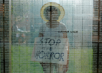 "Doris Tennant walks through the Holocaust Memorial carrying a sign reading ""Stop the Horror"" in Boston"
