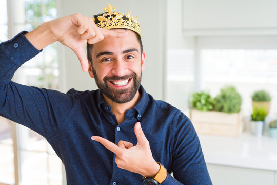 Handsome hispanic man wearing golden crown over head as the king smiling making frame with hands and fingers with happy face. Creativity and photography concept.