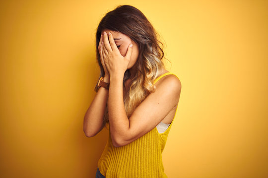 Young beautiful woman wearing t-shirt over yellow isolated background with sad expression covering face with hands while crying. Depression concept.