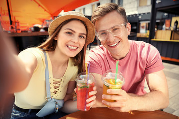 Young couple with summer drinks taking selfie in street cafe