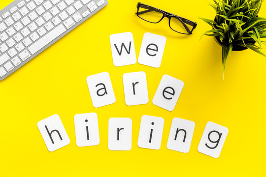 We are hiring copy on work place with keyboard and glass on yellow desk background top view