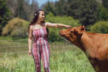 Mixed race young woman feeds cows on a farm Wall mural