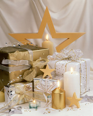 A layout of holiday gifts with candles and stars