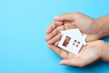 Paper house in hand palm on blue background for real estate property industry