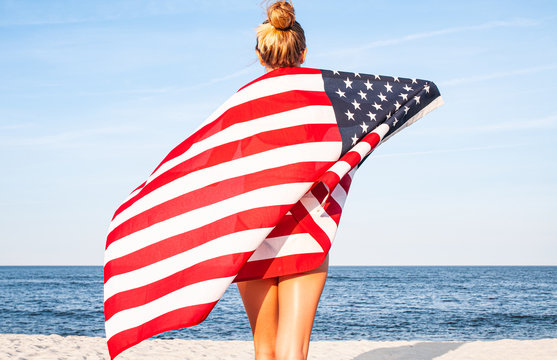 Beautiful patriotic woman with American flag on the beach.  USA Independence day, 4th July. Freedom concept.