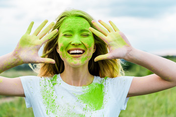 cheerful woman with closed eyes and green holi paint on hands gesturing and smiling outdoors Wall mural