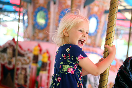 Happy Little Kid Riding Carousel at Carnival