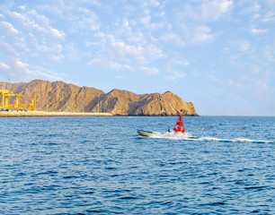 Speed fishing boat moving right next to a red buoy near Muttrah Port, Muscat, Oman.