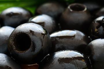 Marinated black olives on wooden background