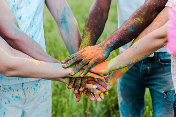 cropped view of multicultural friends with colorful holi paints putting hands together
