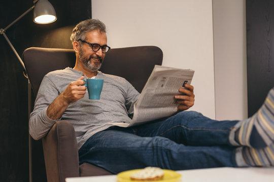 man reading newspaper at his apartment