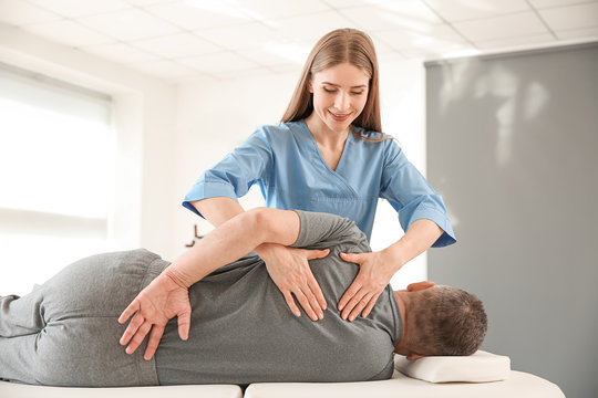 Physiotherapist working with mature patient in rehabilitation center