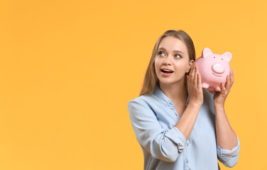 Young woman with piggy bank on color background Wall mural