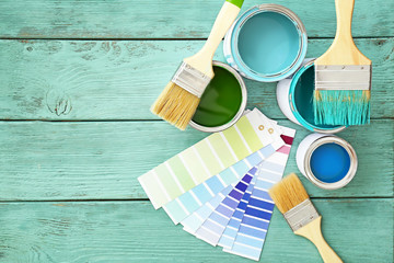 Cans of paint with brushes and palette samples on wooden background Wall mural