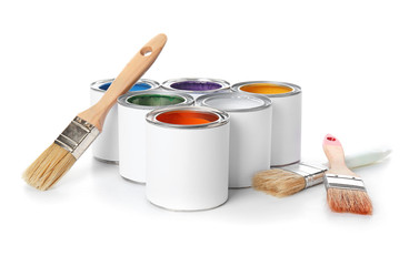 Cans of paints with brushes on color background