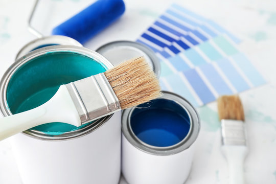 Cans of paint with brush on table, closeup
