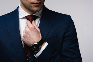 partial view of businessman touching tie isolated on grey