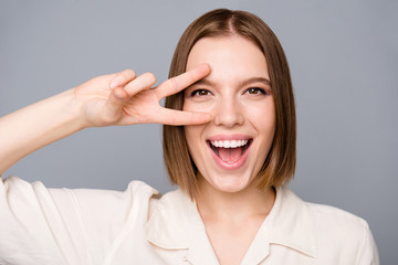 Close up photo of lovely charming attractive lady make v-signs have free time laugh scream shouyt dressed fashionable blouse isolated gey background