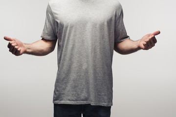 partial view of man in grey shirt showing thumbs up isolated on grey, human emotion and expression concept