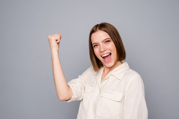 Porrait of charming cute nice pretty youth raise fists shout yeah hooray conquer prize isolated wear fashionable clothing isolated grey silver background