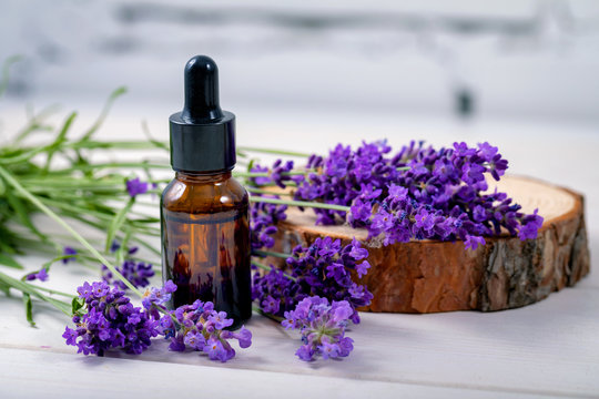 lavender herbal oil and flowers on wooden background