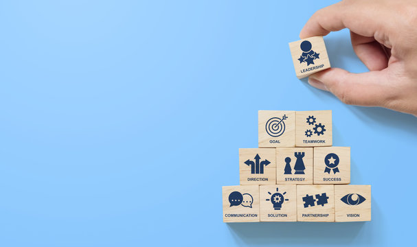 Hand arranging wood block stacking pyramid with icon leader business on blue background. Key success factors for leadership elements concept