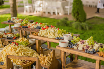 Foto op Canvas Buffet, Bar Food at the event, wedding reception with a variety of cheese, fruits, nuts and breads laid out on wooden stands