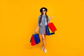 Full length body size view photo charming cute lady fashionable trendy stylish hold hand retail variety colorful travel free time long haircut striped denim outfit jeans isolated yellow background