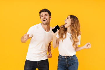 Portrait of delighted couple man and woman in basic t-shirts singing while using smartphone and earphones together Fotobehang